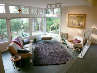 Alternate view of living room and wall of windows overlooking the terraced backyard oasis.