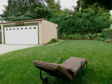 Beautiful pool-sized backyard with flowers, stone pathway to clothesline, and a finished 2-car detached garage with new roof.