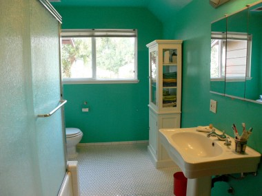 Spacious master bathroom with tile floor and pedestal sink.