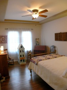 Secondary bedroom with original hardwood floors, tray ceiling, and a small walk-in closet.
