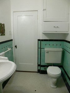 Alternate view of  hallway bathroom with cabinetry, original tile floor and original tile on walls.