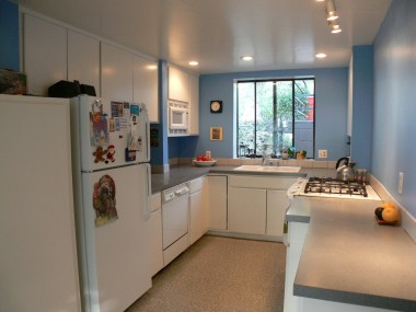 Kitchen with track and recessed lighting, dishwasher, gas stove, and lots of cabinetry, in addition to a pantry.