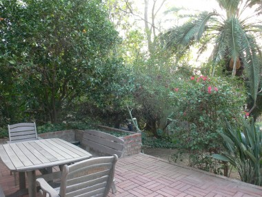 Additional entertaining area on second level of yard, surrounded by lush landscaping and pomegranate tree.