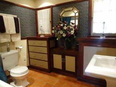 Remodeled downstairs full bathroom with pedestal sink and original built-in cabinetry.