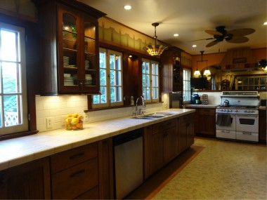 Remodeled kitchen with built-in wine rack, tiled counter top, dishwasher, and refurbished antique stove.