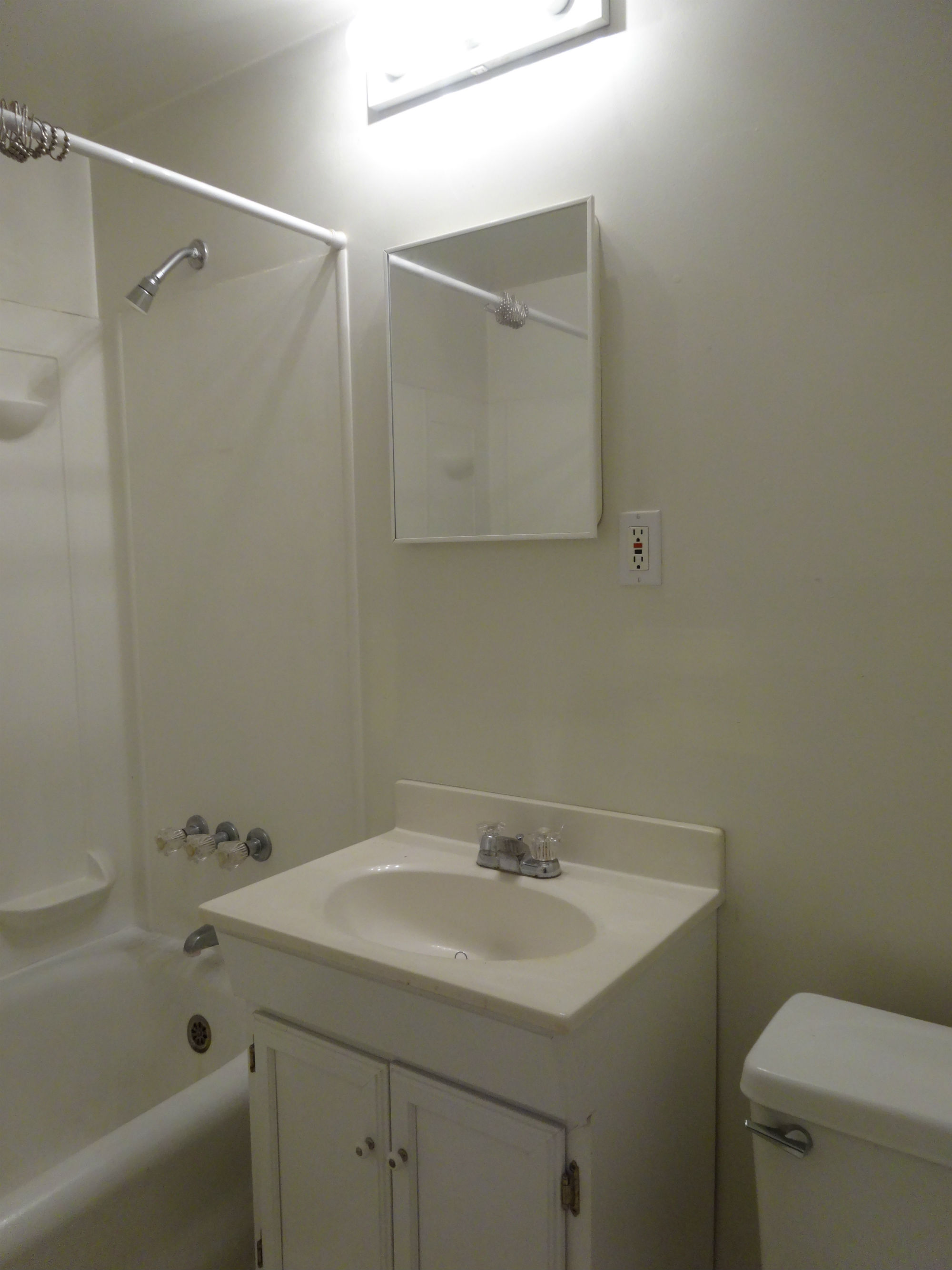 Left side bathroom with newer vanity and toilet.