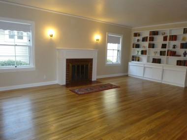 Spacious living room with newly scraped ceiling, refinished original hardwood floors, wood-burning fireplace and shelving.