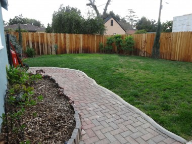 Pool-sized backyard with brick walkway  to large fenced area behind garage.