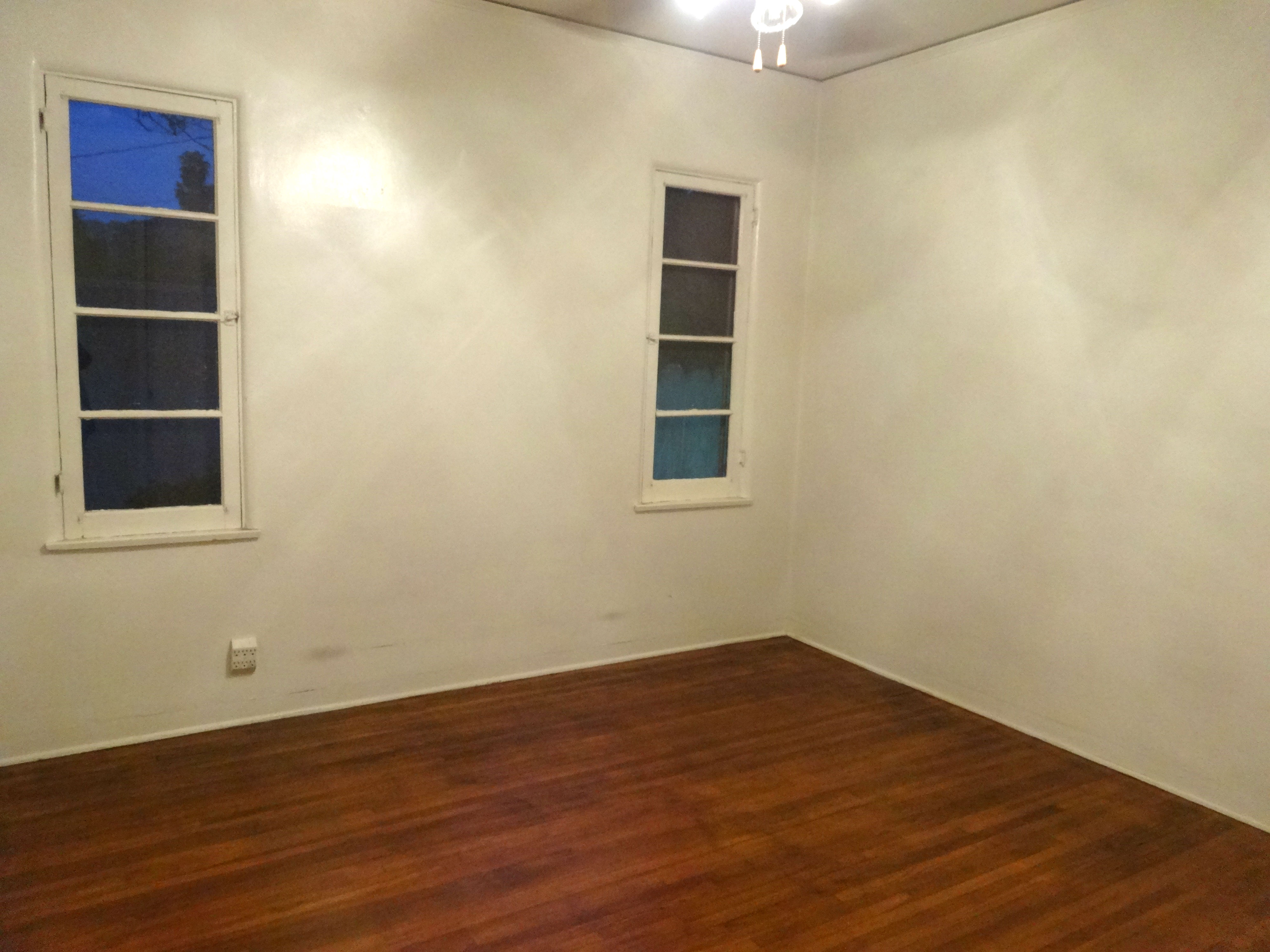 One of four bedrooms total (two in each unit).  Three have exposed original hardwood floors;  one has carpeting.