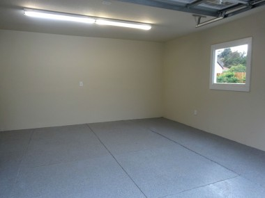 Entire garage has been drywalled, with  an epoxy floor and a window which  allows natural light to flow inward.