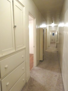 Hallway with linen closet and gas wall heater, looking towards the front entrance and living room.