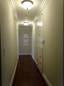 Hallway with linen closet, newer digital  thermostat, great lighting, and original  charming built-in hallway nook.