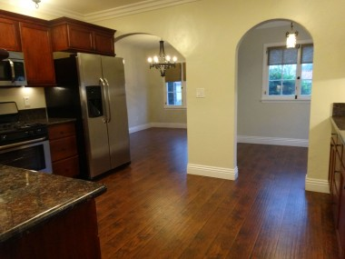 View of kitchen from laundry room. Left  arch leads to formal dining room. Right  arch leads to breakfast nook.
