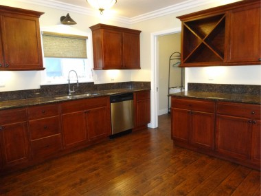 Remodeled kitchen with cherry stained  cabinetry, stainless steel appliances,  granite counter tops, and wine rack.