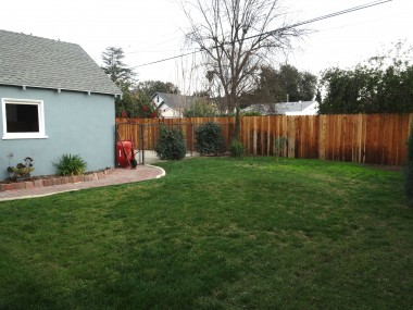 Alternate view of pool-sized yard and  fenced area behind garage.