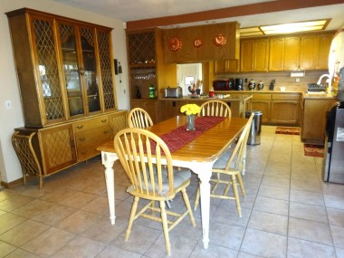 Family dining area and kitchen with lots of cabinetry, built-in wine rack, and tile floor.
