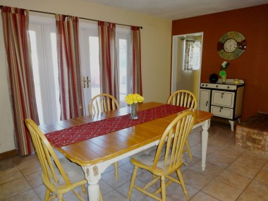 Alternate view of dining area with tile floor and newer double pane French doors leading to backyard.