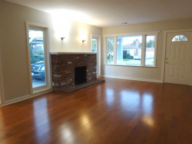 Spacious living room with brand new wood floors and wood-burning fireplace.