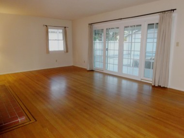 Large living room with newer  double-pane slider doors to covered  patio and huge pool-size yard.
