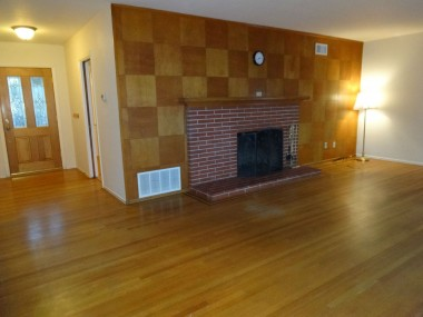 Alternate view of living room with  wood-burning fireplace and original  hardwood floors.