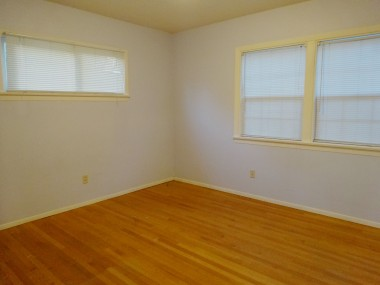 One of the three bedrooms, all with  original hardwood floors exposed.