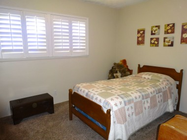 Secondary bedroom with newer  carpeting and plantation shutters.
