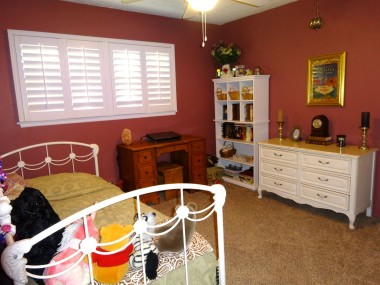 Secondary bedroom with newer  carpeting, ceiling fan, and plantation  shutters