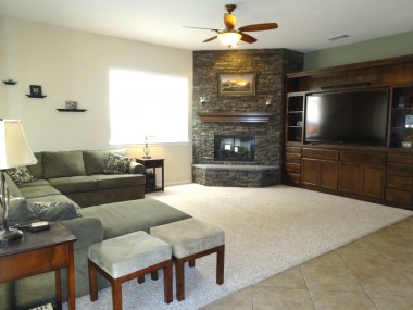 Huge family room with corner fireplace,  custom built-in entertainment center  and carpeting that looks brand new!