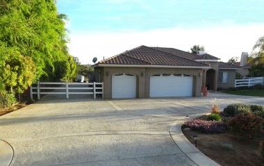 View of paved and lighted side driveway which leads to the massive backyard! 3-car attached garage for the car enthusiast!