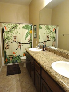 Full hallway bathroom with dual sinks and granite counter.