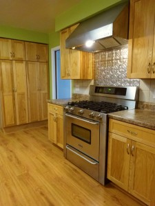 Stainless steel gas stove and large  pantry in background.
