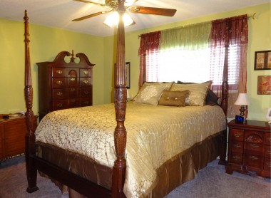 Master bedroom suite with ceiling fan,  newer carpeting, large closet, and  private bathroom.