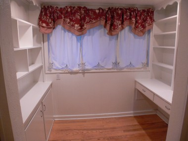 Office nook with built-in shelving, desk and drawers.
