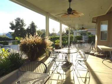 Alternate view of covered patio as the  sun is setting. Lovely plants, trees in the  distance, and the trickling sound of the  pool's waterfall. Just lovely....