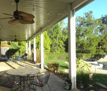 Large covered patio with ceiling fans  and view of lovely backyard. Lots of  mature trees separating this house from  neighboring property.