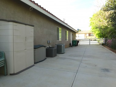 Wide paved driveway along side of  home.