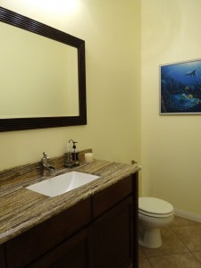 Convenient guest powder room just off the front living area with granite counter.