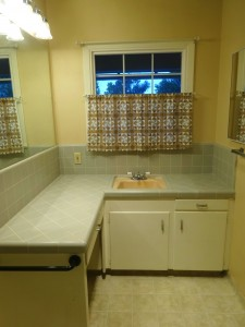 Three-quarter bathroom with original  counter and shower tile in like-new  condition.