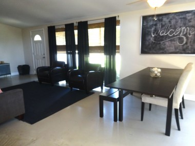Indoor dining area with sliding door to convenient outdoor BBQ area on side of house.