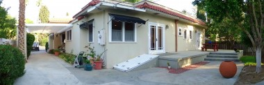 Panoramic view of driveway, back of house, back patio, and part of yard.