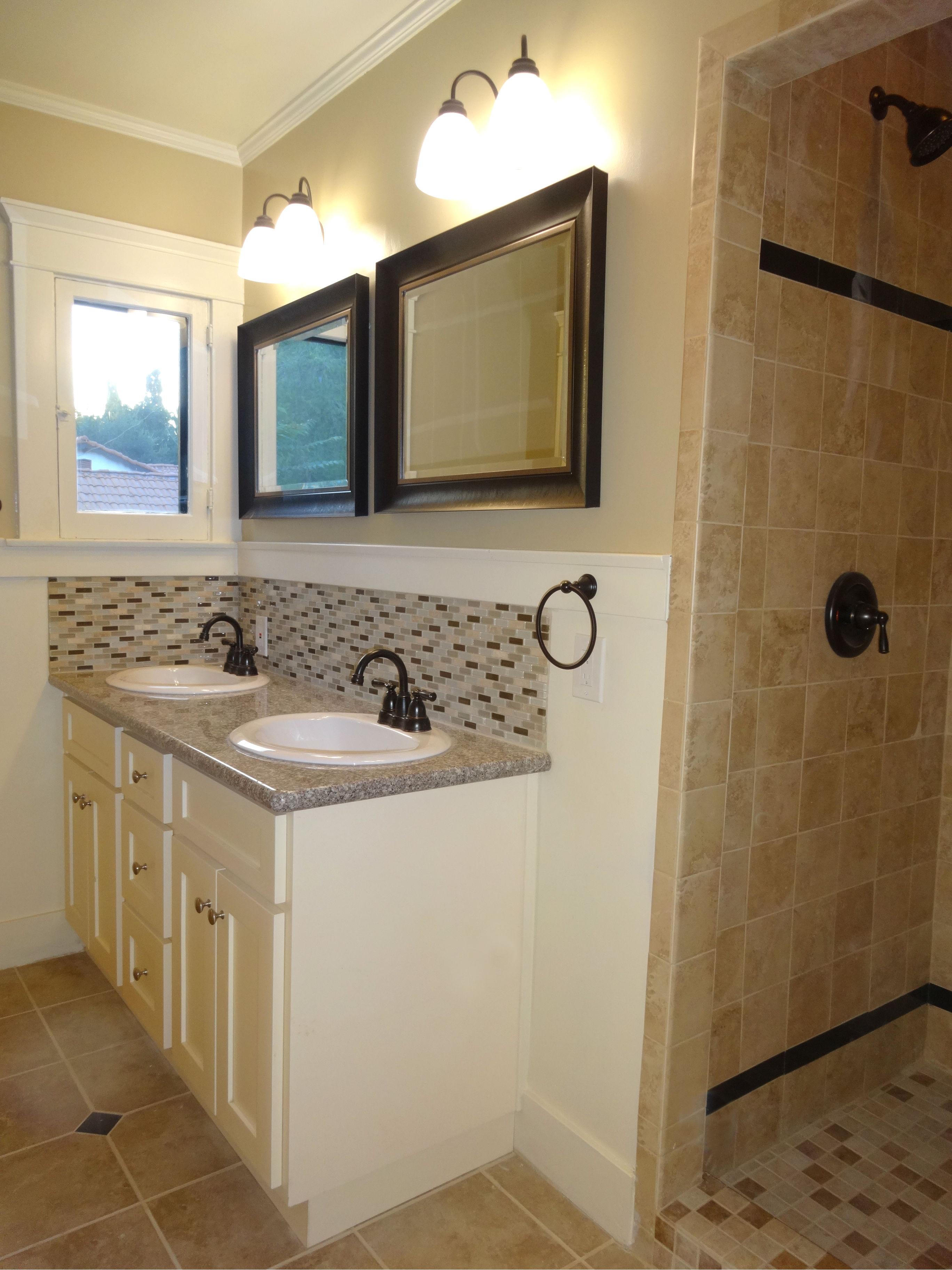 Completely remodeled bathroom with tile floor, granite counter, tile back splash, tiled shower enclosure, and dual sinks.
