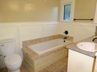 Remodeled bathroom with new toilet, new tub, tile floor, etc.