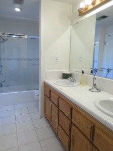 Downstairs convenient bathroom with glass shower doors, tile flooring, and dual sinks.
