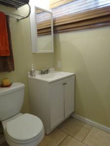 Hallway bathroom with tub and tile flooring.