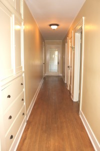 Hallway, with linen closet, leading to two bedrooms and front porch area.