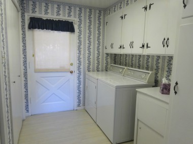Large indoor laundry room with lots of cabinetry, utility sink, and pantry!