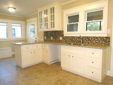 Completely remodeled kitchen with granite counters, tile floor, tile back splash, and built-in nook storage seating.