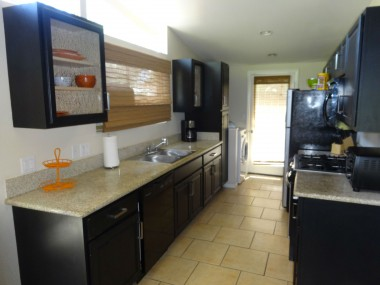 Remodeled kitchen with granite counter tops, dishwasher, stainless steel gas stove, glass-fronted cabinets, and convenient indoor laundry facilities.