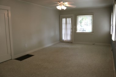 Living room with ceiling fan, window  blinds, and berber carpeting (with  hardwood floors underneath). Newer  central air/heat too!