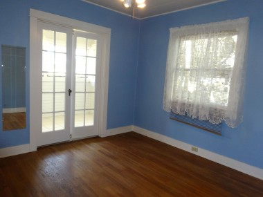 Back bedroom with ceiling fan,  hardwood floors, and French doors  leading to convenient bonus room (which  has separate access through laundry  room, so this isn't the only access).